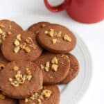 It's vegan cookies made from cacao and walnut on a plate along with a cup of coffee.