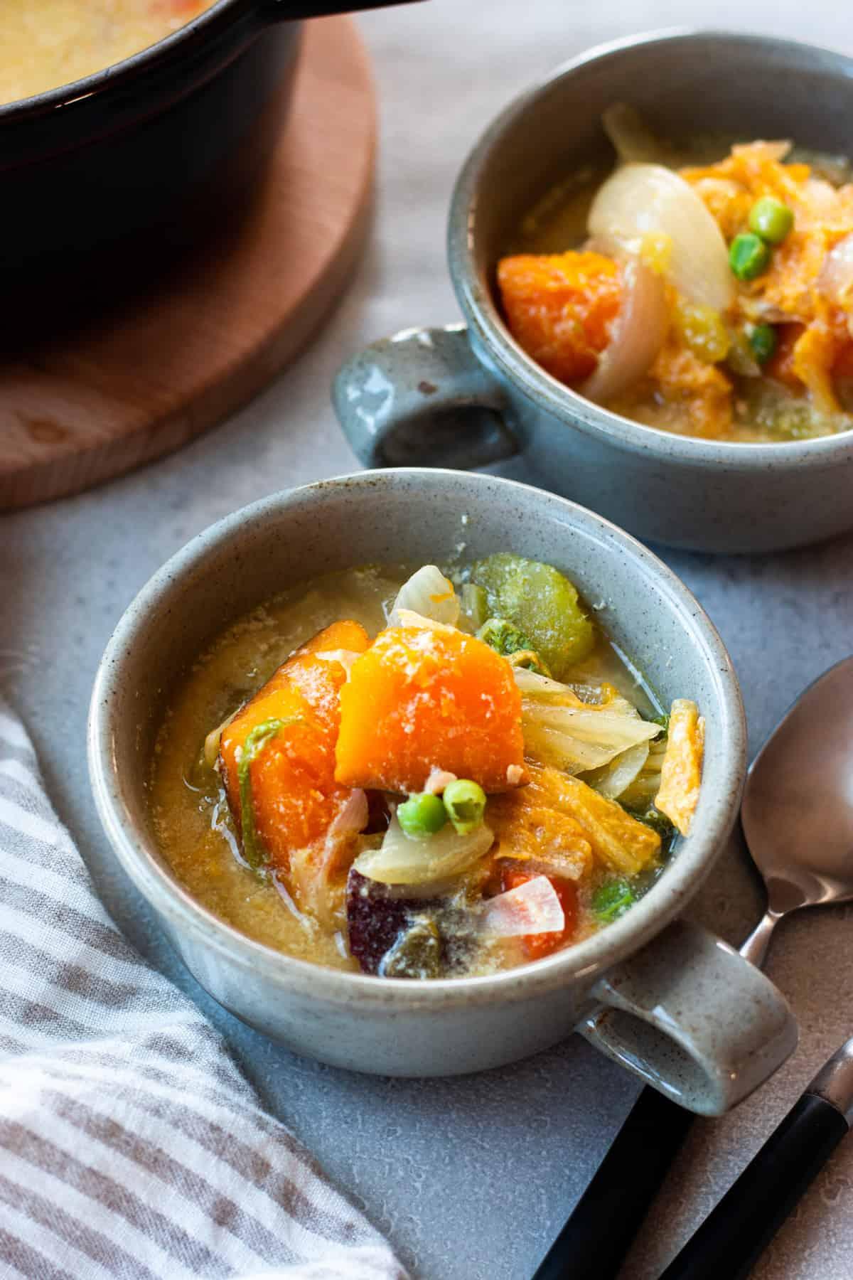 スープ皿に取り分けられたかぼちゃと豆乳の味噌汁。かぼちゃ、グリーンピース、白菜など野菜たっぷりのスープ。