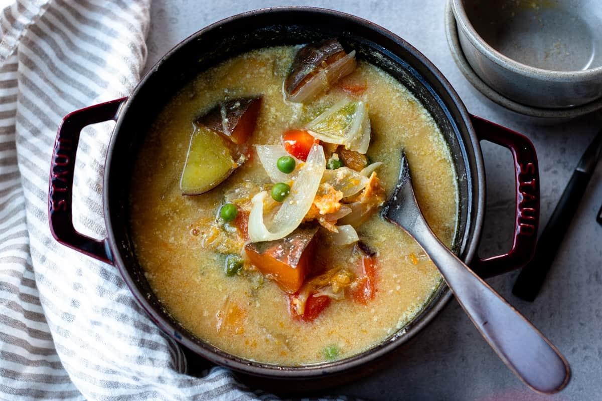ストウブ鍋に入ったかぼちゃと豆乳の味噌汁。かぼちゃ、グリーンピース、白菜など野菜たっぷりのスープ。