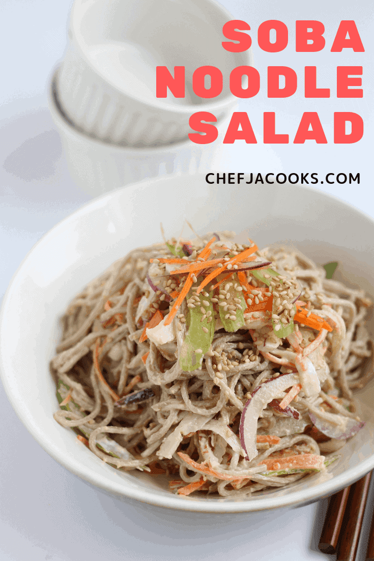 Soba noodle salad in a bowl with carrot, red onion, celery and sesame seeds.
