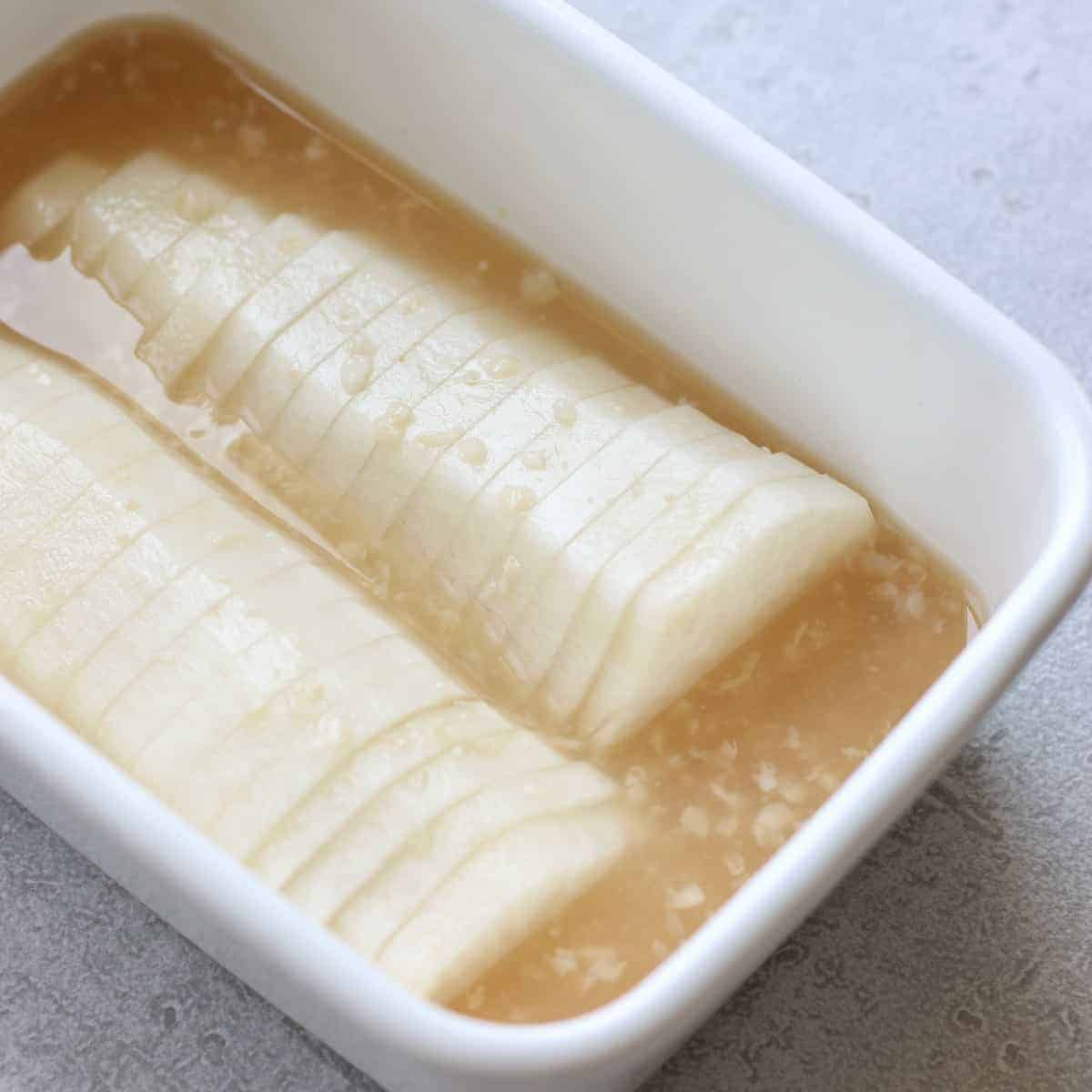 pickled daikon in a white container