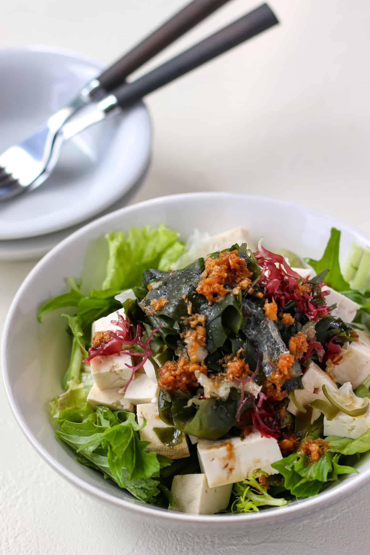 深皿に盛り付けられた、緑野菜と、豆腐、海藻。生姜ドレッシングがトッピングされている。