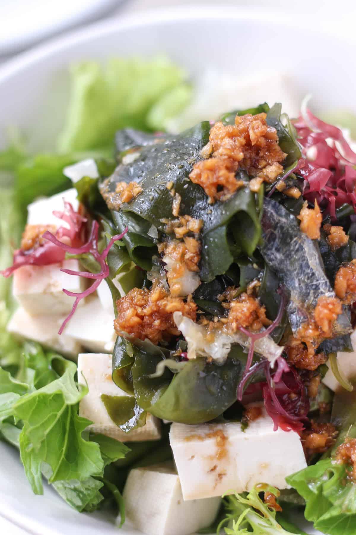 深皿に盛り付けられた、緑野菜と、豆腐、海藻。生姜と醤油のドレッシングがトッピングされている。
