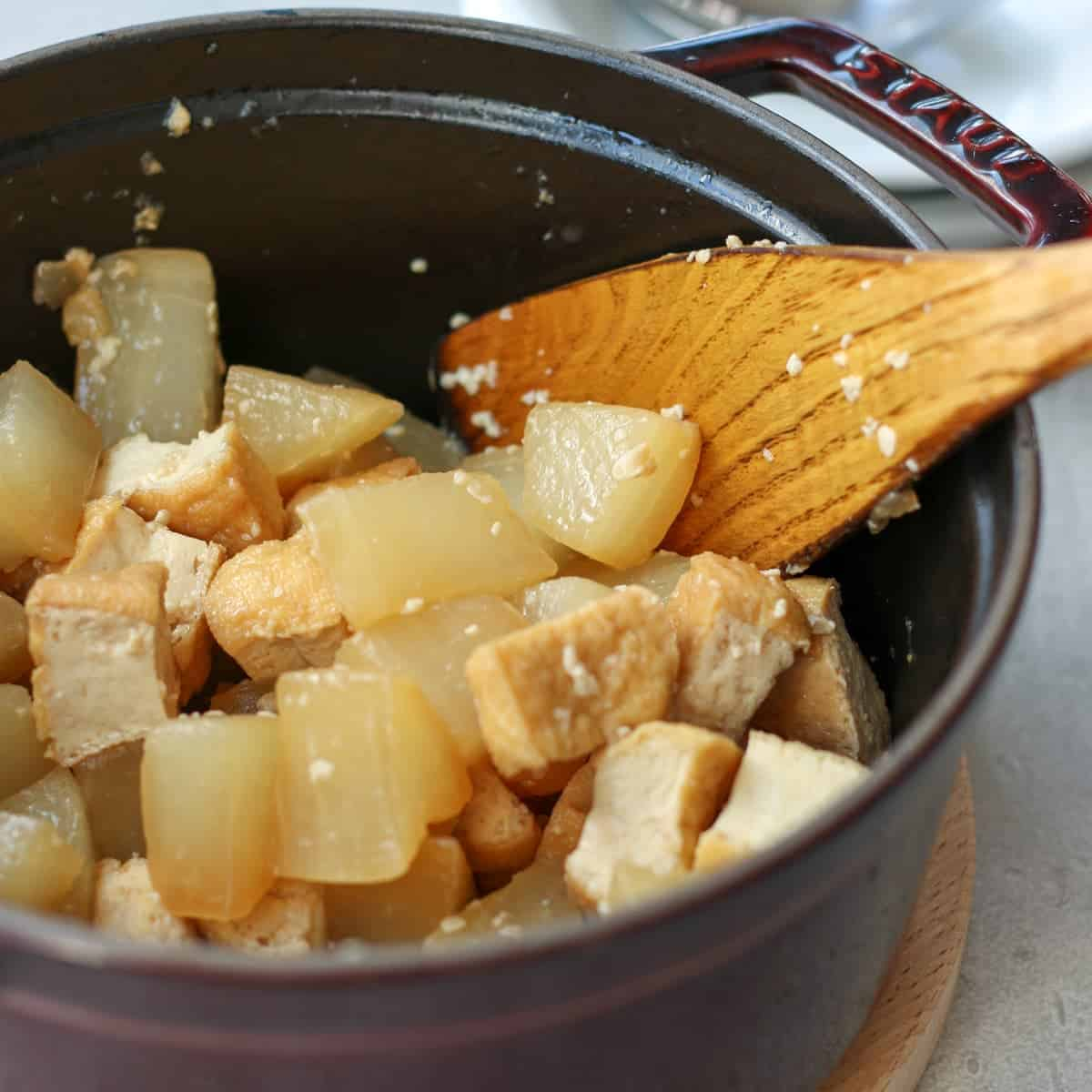 simmered daikon in a pot with spatula