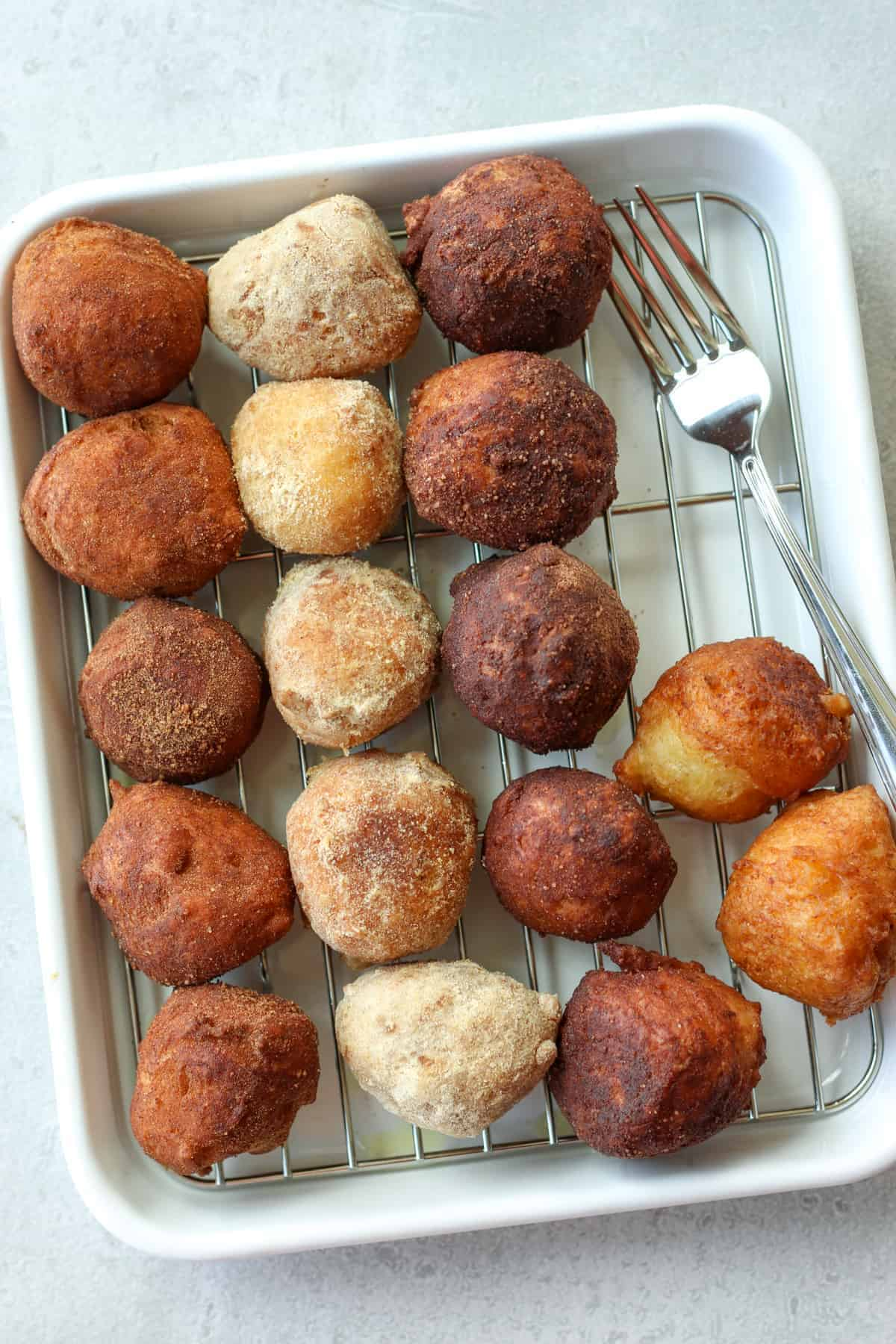 many tofu donut balls with 3 sugar toppings on a tray