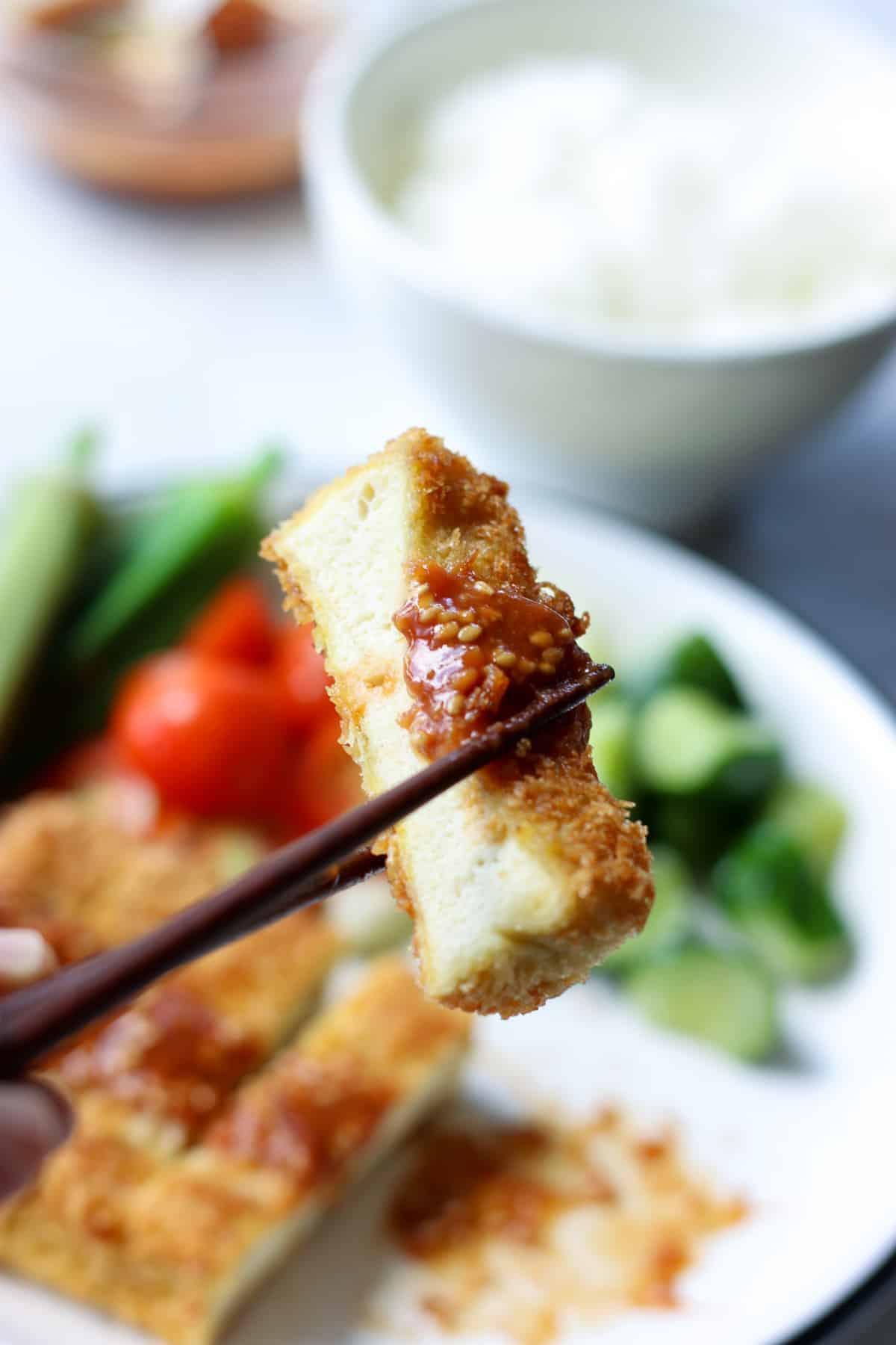 高野豆腐カツ一切れを箸でつまんだ様子