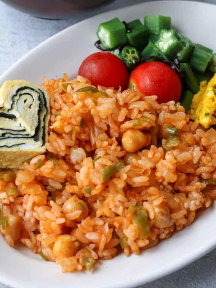 ketchup rice on a plate served with tamagoyaki and salad