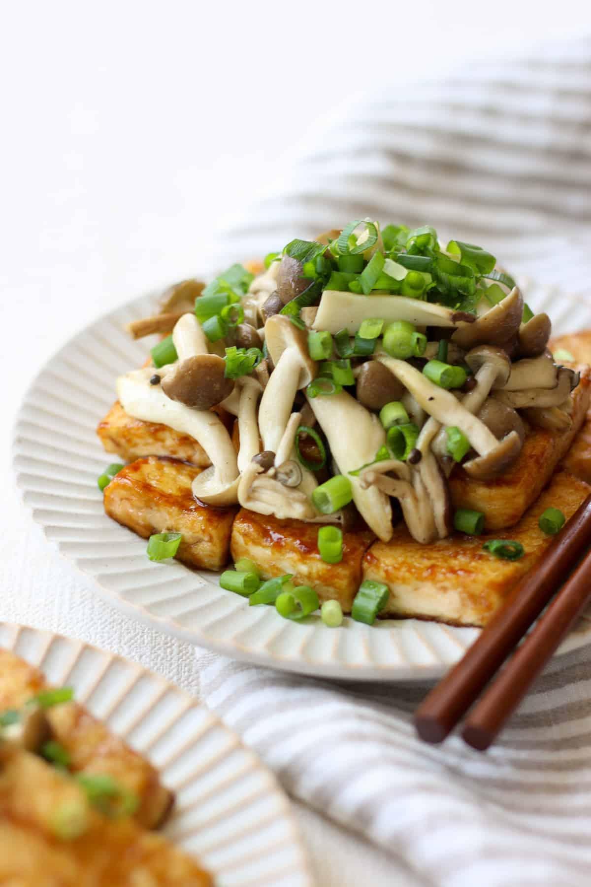 Teriyaki tofu and mushrooms on a plate with chopsticks